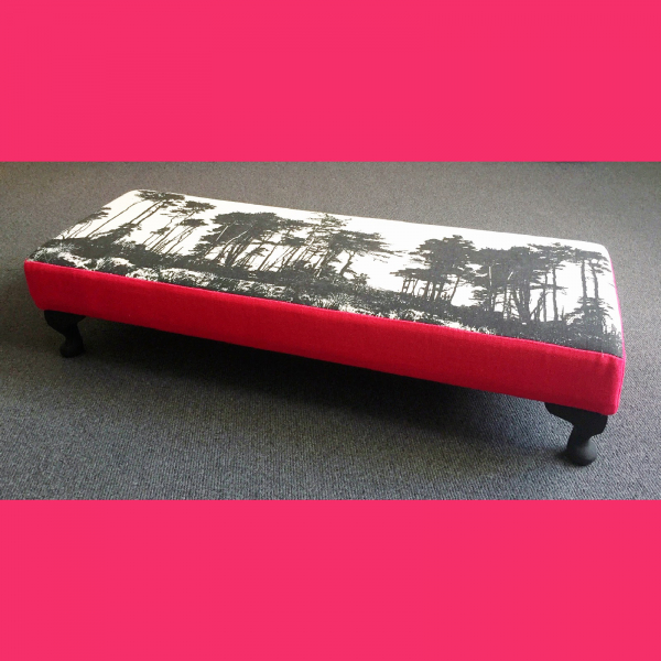 Long low upholstered footstool in black white pink fabric